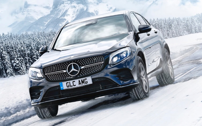 Mercedes-Benz GLC AMG driving through winter weather.