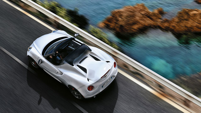 Alfa Romeo 4c Spider driving along a coastal road.