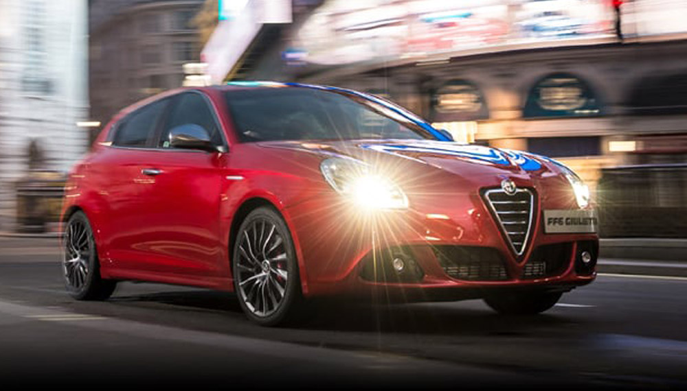 Red Alfa Romeo Giulietta driving down a city street.
