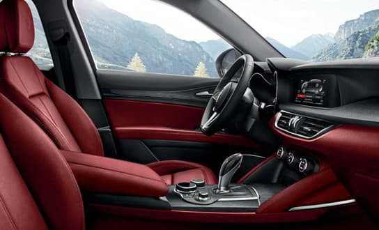 Giulia interior showing red leather seats and leather steering wheel.