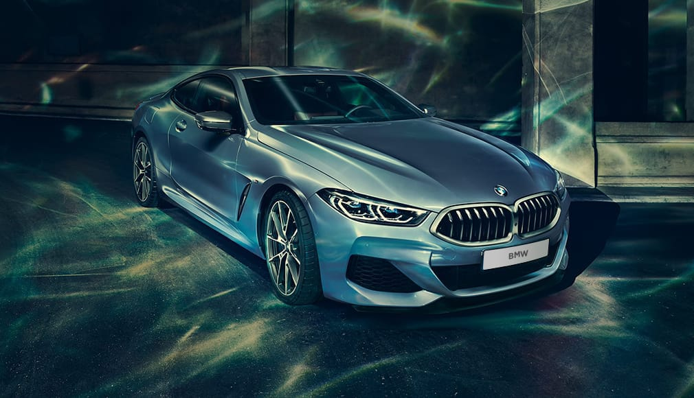 Silver BMW 8 Series in a garage with blue lighting.