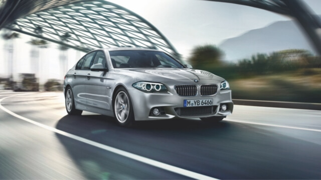 BMW 5 Series driving on modern road