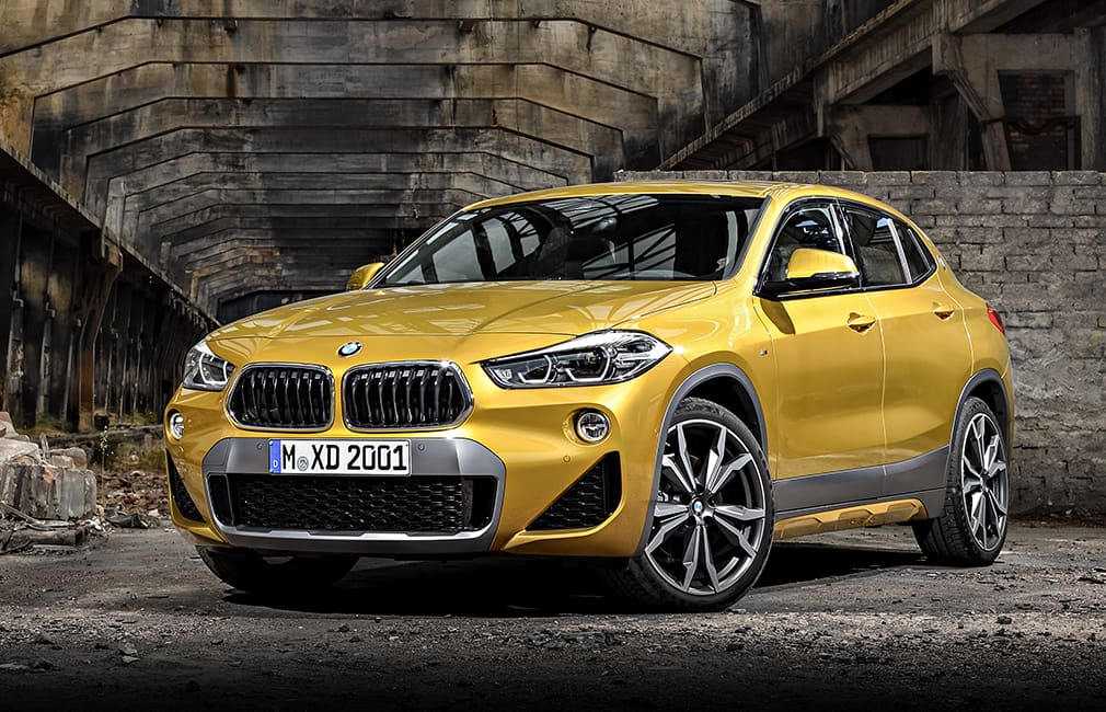 Gold BMW x2 parked inside an abandonded warehouse.