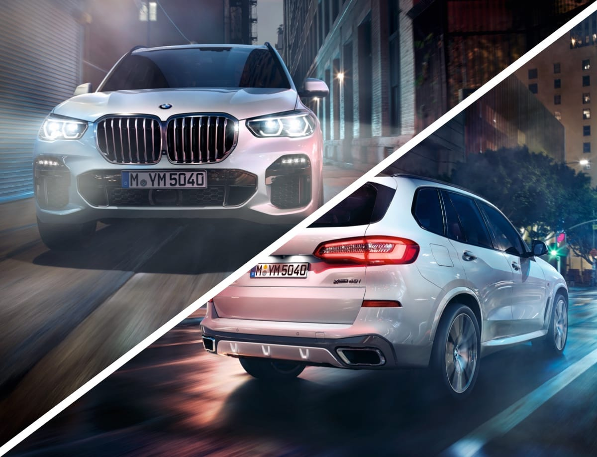 A white BMW X5 driving through a city.