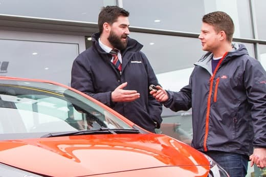 Sales executive handing keys to a customer outside showroom