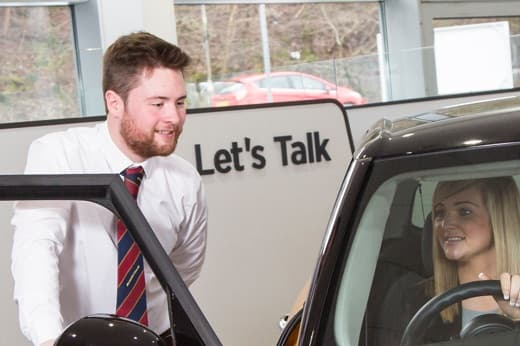 Sales executive showing a customer cars