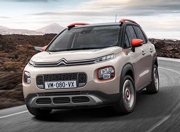 Citroen C3 Aircross driving down a road.