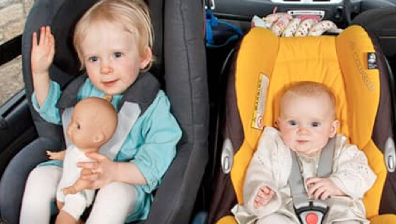 Childeren strapped safely into car seat in the back of car
