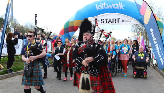 Bagpiper leading the Kilkwalk over the start line