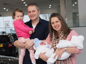 Happy family in Arnold Clark car showroom