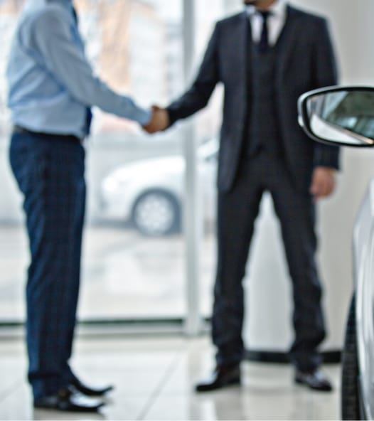 Two male car salesmen in showroom