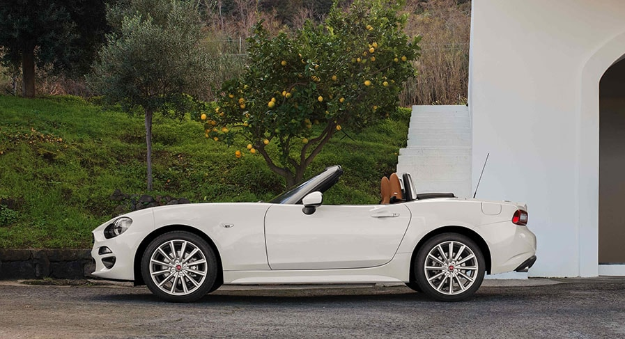 White Fiat 124 Spider parked on gravel