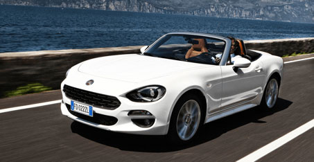 White Fiat 124 Spider driving along coast