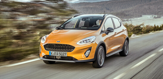 Orange Fiesta Active driving down a country road.