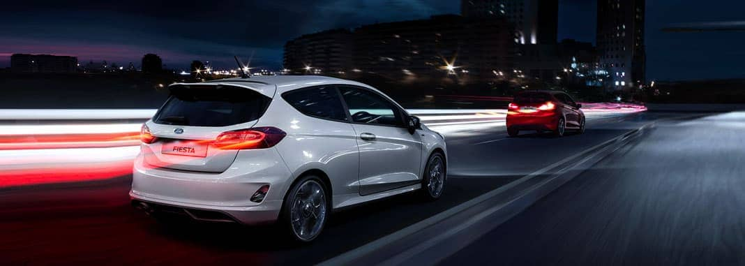 White Ford Fiesta in the city at night.