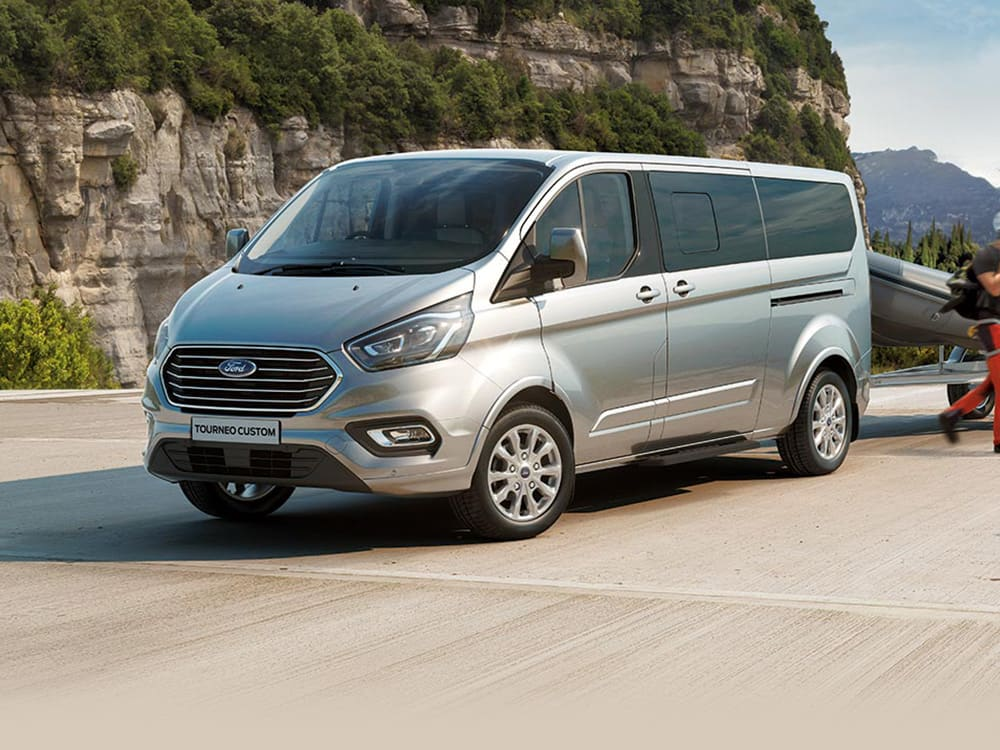 Silver Ford Transit Tourneo 2018 parked at the beach with walkers sitting at the side.