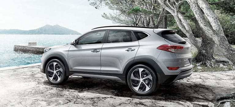 Metallic brown Hyundai Tucson with shiny alloy wheels.