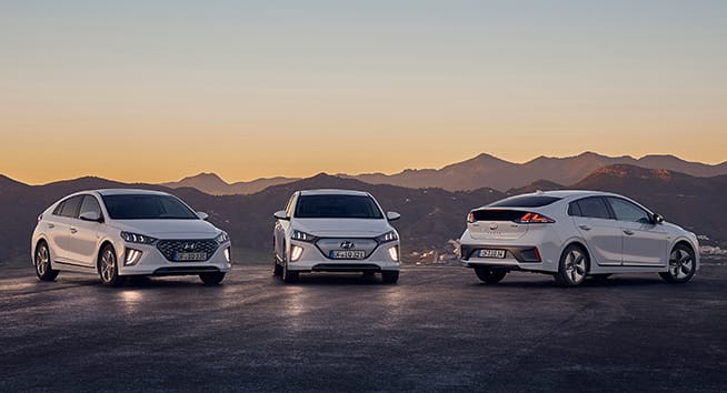 Three white Hyundai IONIQ in the morning sun.