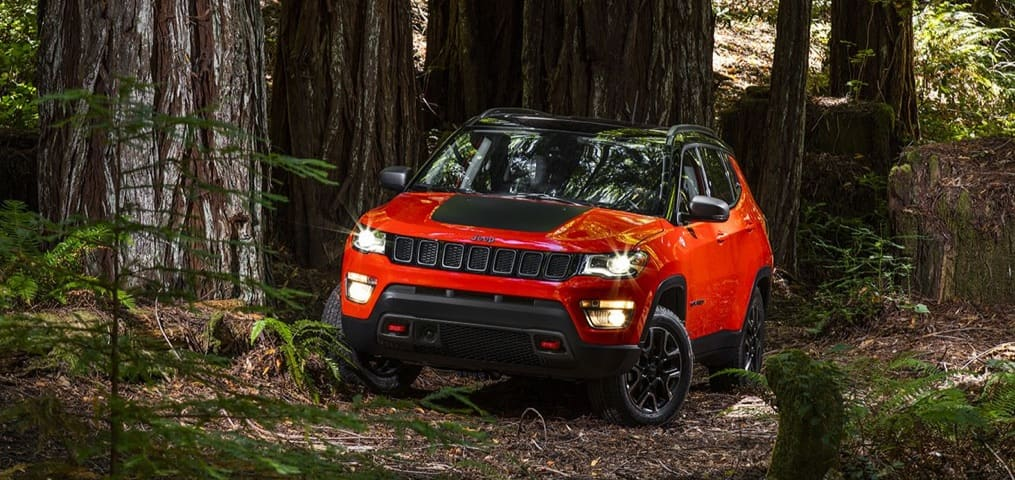 Red and Black Jeep Compass trailing through the woods with its lights on.