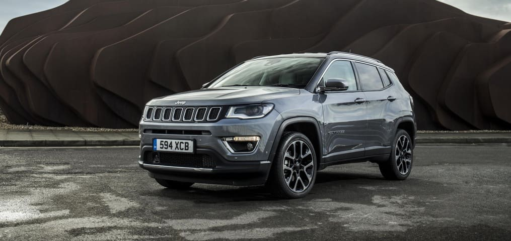 Grey and Black Jeep Compass parked in empty ground with Stone artwork behind it.