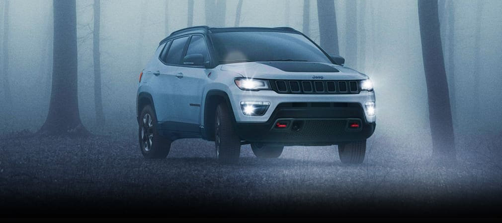 White and Black Jeep Compass trailing through a dark foggy forest at night.