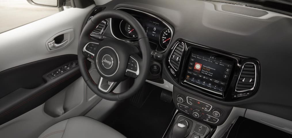 Jeep Compass leather interior and Uconnect digital screen.
