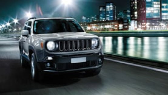 Jeep Renegade driving along a city river.