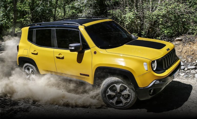 Yellow Jeep Renegade driving on dusty rugged terrain.
