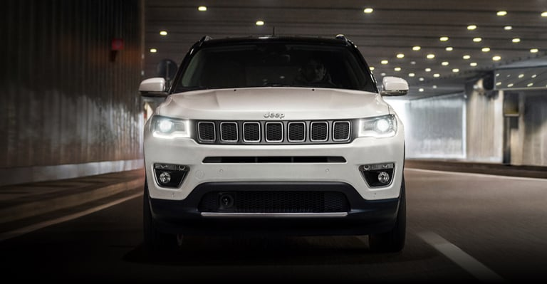 Side view of a white Jeep Compass