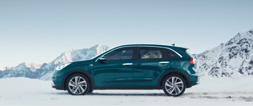 Blue Kia Niro in snow