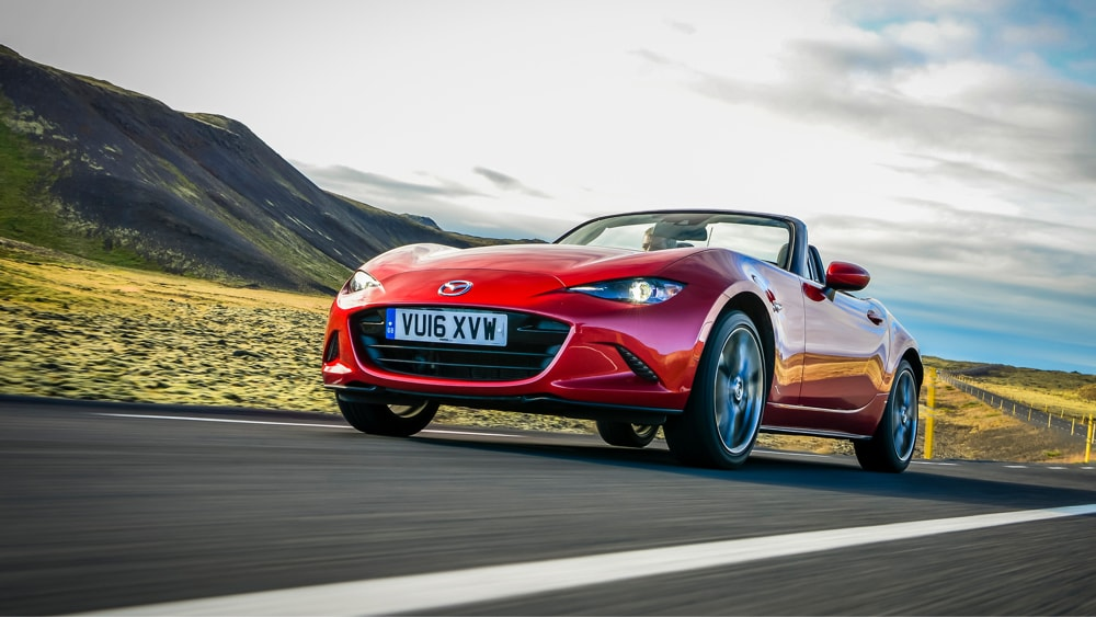 Red Mazda MX-5 driving on scenic road