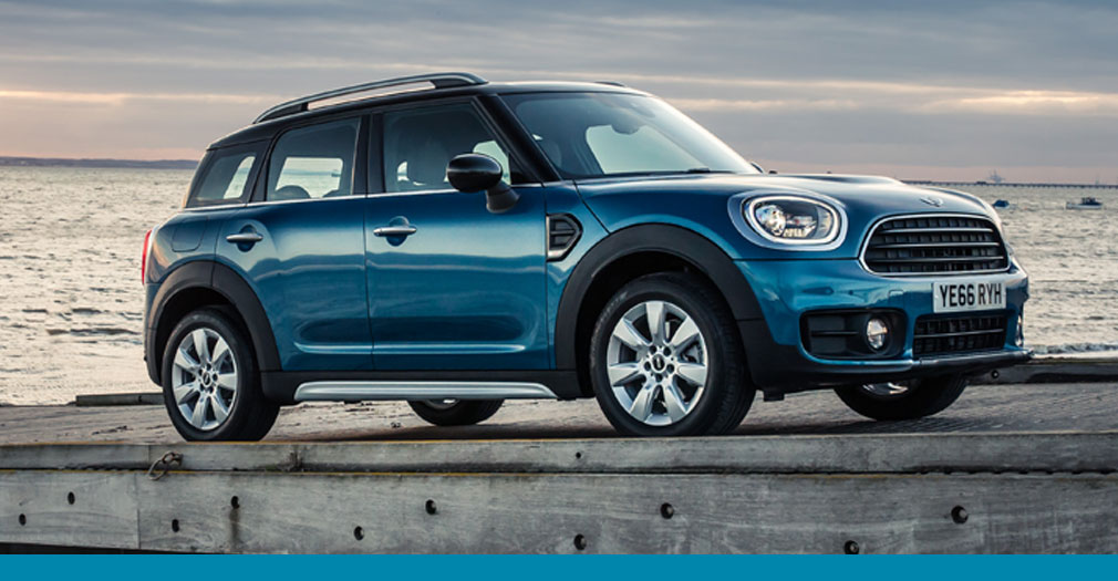 Blue MINI countryman parked on a pier with the sun setting.