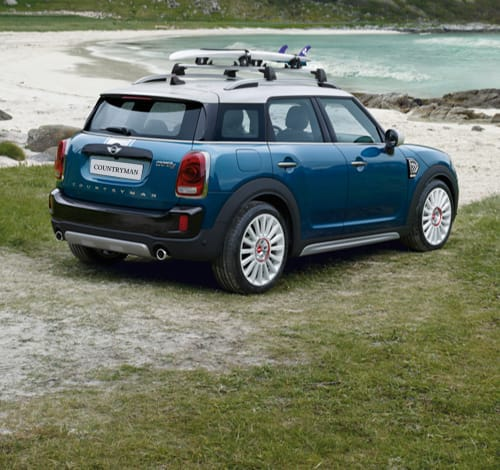 Blue MINI Countryman on the beach with a surfboard on the roof.