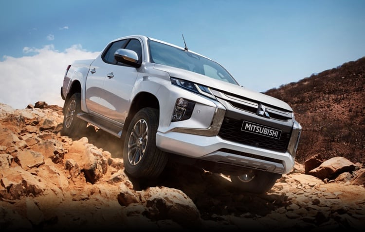 Silver Mitsubishi L200 driving on a muddy landscape