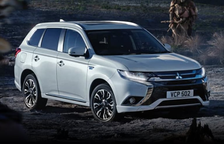 Silver Mitsubishi Outlander PHEV parked on dusty grassland