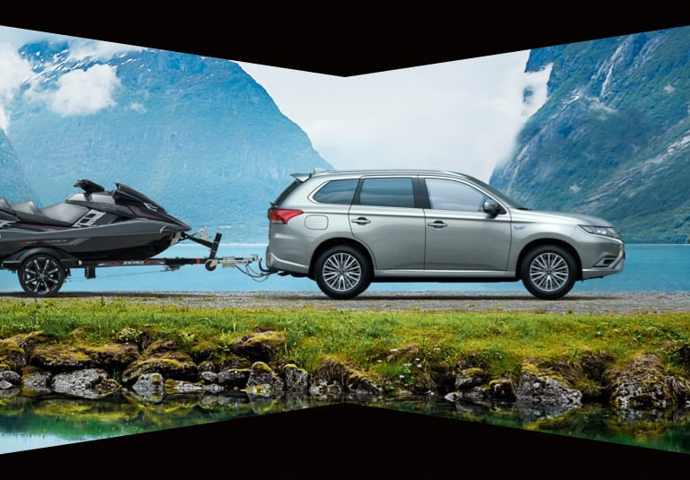 Mitsubishi Outlander PHEV towing a jet ski in front of a lake