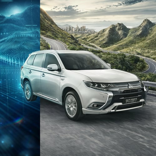 Silver Outlander PHEV driving through a mountain range