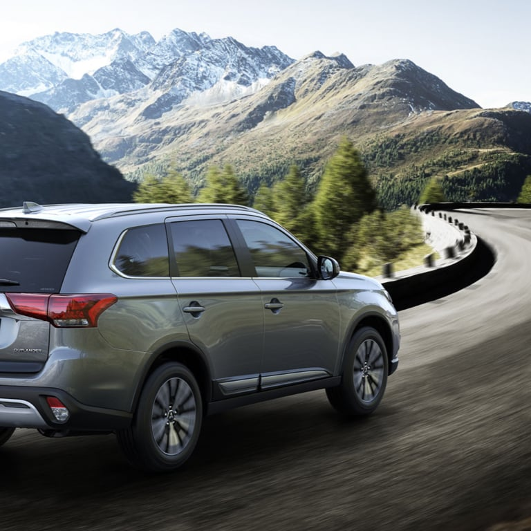 Rear view of an Outlander PHEV driving through a mountain range