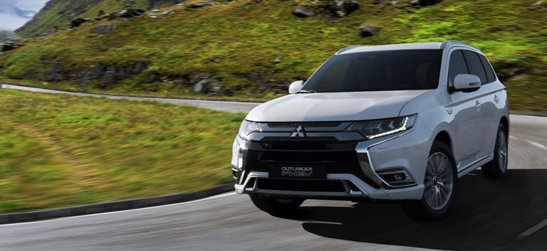 Front view of the Outlander PHEV driving round a hairpin bend