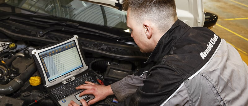 Technician running diagnostics on a car engine