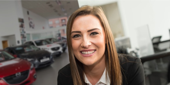 Young woman smiling in car showroom
