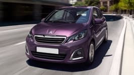 Purple Peugeot 108 driving down a street