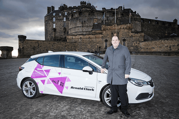 A man standing next to a car with a pink Saltire and the Arnold Clark logo printed on the side of it.