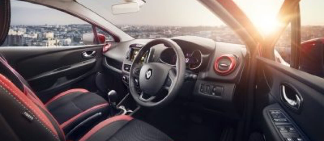 Interior of a red Renault Clio with a city landscape and setting sun