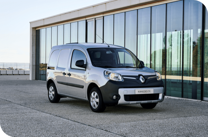 Silver Renault Kangoo parked infront of glass building