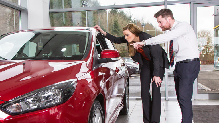 Salesman showing young woman a new car