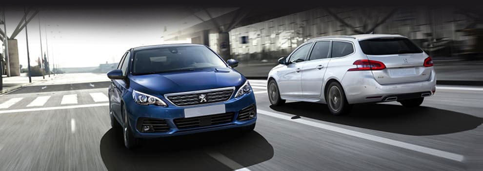 Blue Peugeot 308 hatchback and Silver Peugeot 308 SW driving opposite ways in the city