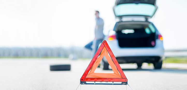 Car parked at the side of a road with a roadside warning triangle in focus