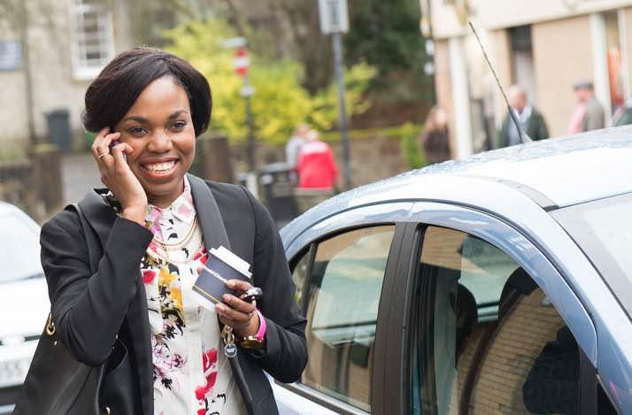 Woman on phone standing next to her car with a coffee cup