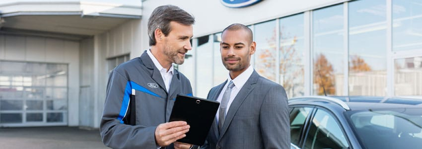 Ford technician showing checklist to customer outside branch